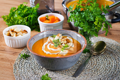 Pumpkin soup in a bowl served with parsley and croutons. Vegan soup. Thanksgiving day food. Halloween meal.