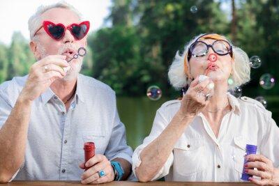 Plakat Puszczać bańki. Aktywna śmieszna starzejąca się para stoi wpólnie i dmucha mydlanych bąble
