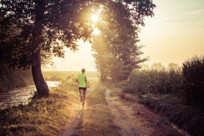 Plakat Ragazzo che corre all'alba su strada di campagna in estate