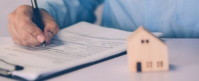 Plakat Real estate agent holding home and signing contract about agreement of real property on desk, house broker and planning investment, businessman writing on document form rent house, business concept.