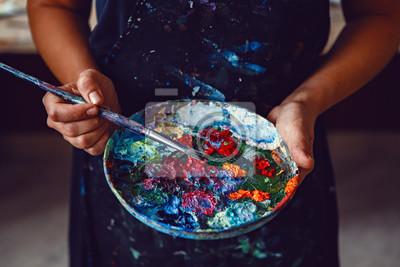 Plakat Ręce artystki trzyma brudną paletę z różnymi farbami i pędzelami w studio artystycznym. Styl życia i koncepcja hobby
