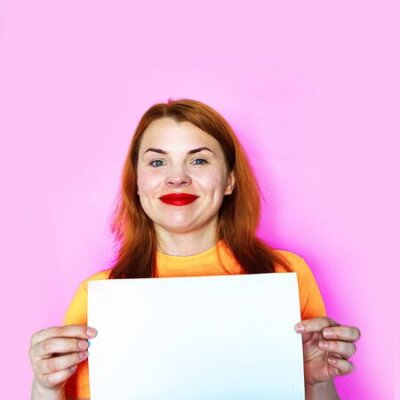 Plakat Redhead girl is holding white mockup blank on pink background