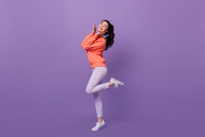 Plakat Refined asian woman standing on one leg. Full length view of blissful chinese girl dancing on purple background.