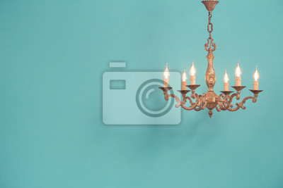 Plakat Retro antique old bronze chandelier with bulb lamps shaped candles hanging front mint blue wall background. Nostalgia lighting concept. Vintage style filtered photo