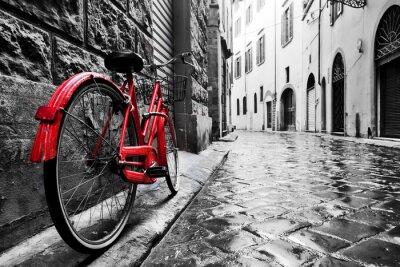 Plakat Retro czerwony rower na brukowanej uliczce na starym mieście. Kolor w czerni i bieli