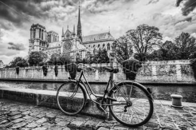 Plakat Retro rower obok katedry Notre Dame w Paryżu, Francji i Sekwanie. Czarno-biały rocznik