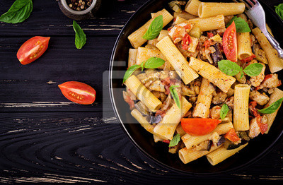 Rigatoni pasta with chicken meat, eggplant in tomato sauce in bowl. Italian cuisine. Top view. Copy space