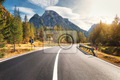 Plakat Road in summer forest at sunset in Italy. Beautiful mountain roadway, trees with green foliage and sunlight. Landscape with empty asphalt road through woodland, blue sky, high rocks. Travel in Europe