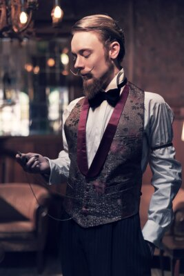 Plakat Rocznika 1900 moda mężczyzna z brodą. Stojąc w starym drewnianym pokoju