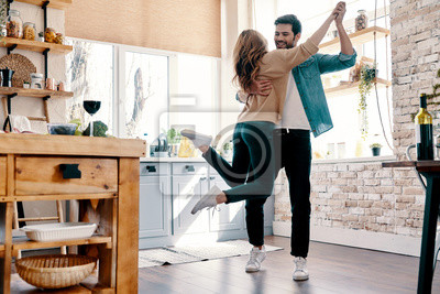 Plakat Romance. Full length of beautiful young couple in casual clothing dancing and smiling while standing in the kitchen at home