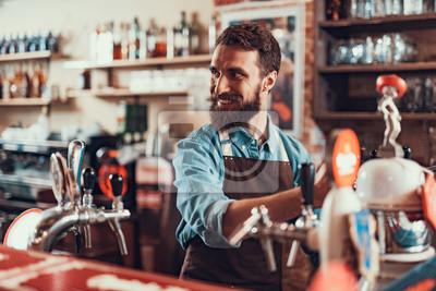 Plakat Rozochocony barman w fartuchu pracuje przy pubem