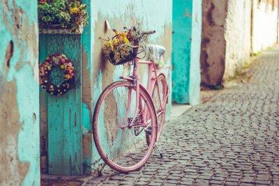 Plakat Różowy rower vintage z koszem pełnym kwiatów obok starego budynku w Hiszpanii