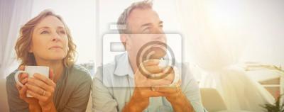 Plakat Rozważny w średnim wieku pary obsiadanie na leżance ma kawę