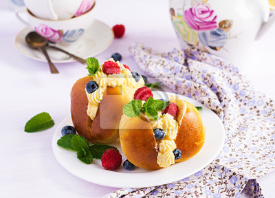 Rum baba decorated with whipped cream and fresh raspberry, blueberry. Savarin with rum, cream and berries. Italian cuisine