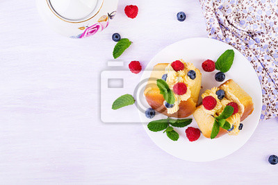 Rum baba decorated with whipped cream and fresh raspberry, blueberry. Savarin with rum, cream and berries. Italian cuisine. Top view