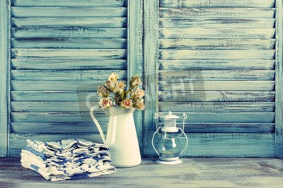 Plakat Rustykalna kuchnia martwa natura: biały dzbanek z kiści róż, ręczniki stos i latarnia przeciwko zabytkowe drewniane okiennice. Filtrowane stonowanych obraz.