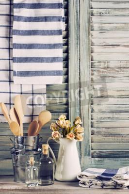 Plakat Rustykalna kuchnia martwa natura: biały dzbanek z róż pęczek ocynkowane wiadra z drewnianymi łyżkami, butelek szklanych i ręczników lnianych przeciwko zabytkowe drewniane okiennice.