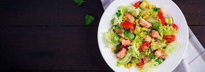 Salad with grilled salmon, lettuce, avocado, tomatoes and corn on a white bowl. Paleo diet. Top view, banner