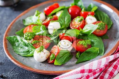 Sałatka caprese. Zdrowy posiłek z pomidorkami cherry, kulkami mozzarelli i bazylią. Domowe, smaczne jedzenie. Koncepcja smacznego i zdrowego posiłku wegetariańskiego.