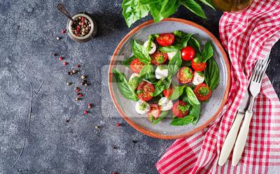 Sałatka caprese. Zdrowy posiłek z pomidorkami cherry, kulkami mozzarelli i bazylią. Domowe, smaczne jedzenie. Koncepcja smacznego i zdrowego posiłku wegetariańskiego. Widok z góry. Płaskie leżało