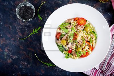Sałatka z makaronem z tuńczykiem, pomidorami, oliwkami, ogórkiem, słodką papryką i rukolą na rustykalnym tle. Widok z góry