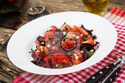 Sałatka z pomidorów z fioletową bazylią i orzeszkami pinii. Wegańskie jedzenie. Włoski posiłek.