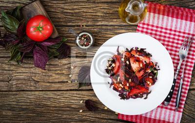 Sałatka z pomidorów z fioletową bazylią i orzeszkami pinii. Wegańskie jedzenie. Włoski posiłek. Widok z góry. Płaskie leżało.