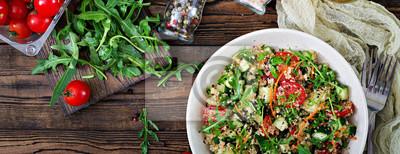 Sałatki z quinoa, arugula, rzodkiewka, pomidory i ogórek w misce na drewniane tła. Zdrowa żywność, dieta, detox i wegetariańska koncepcja. Widok z góry. Płaskie leżało