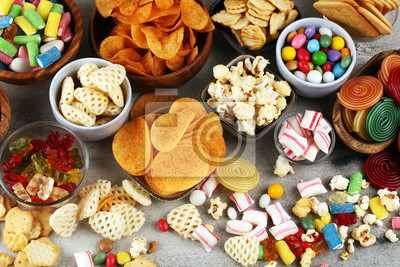 Plakat Salty snacks. Pretzels, chips, crackers and candy sweets on table