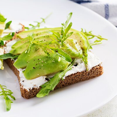 Sandwich of cream cheese bread and slices of avocado on a plate on a light background. Healthy vegetarian food.