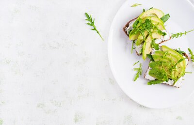 Sandwich of cream cheese bread and slices of avocado on a plate on a light background. Healthy vegetarian food. Top view, overhead, copy space