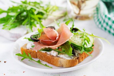 Sandwich with prosciutto, cucumber, black olives, arugula and feta cheese on  table.  Trend food.