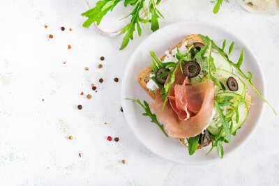 Sandwich with prosciutto, cucumber, black olives, arugula and feta cheese on  table.  Trend food. Top view, flat lay