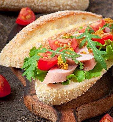 Sandwich with sausage, lettuce, tomato and arugula