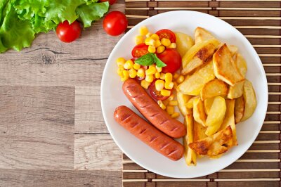 Sausage with fried potatoes and vegetables  on a plate
