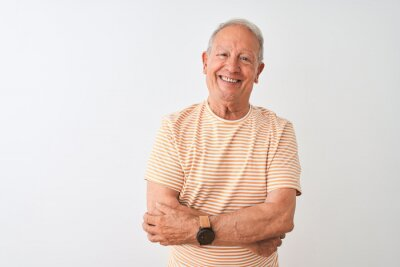 Plakat Senior grey-haired man wearing striped t-shirt standing over isolated white background happy face smiling with crossed arms looking at the camera. Positive person.