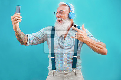 Plakat Senior hipster man using smartphone app for creating playlist with rock music - Trendy tattoo guy having fun with mobile phone technology - Tech and joyful elderly lifestyle concept - Focus on face