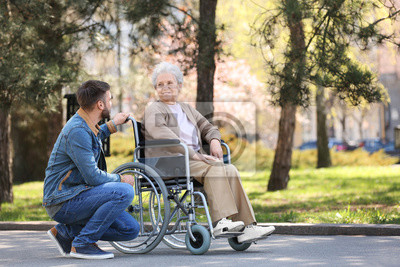 Plakat Senior woman in wheelchair with young man at park