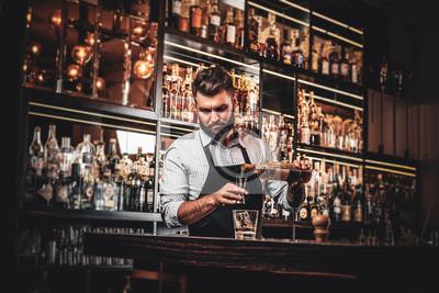 Plakat Serious barman is prepairing drinks for customers at posh bar.