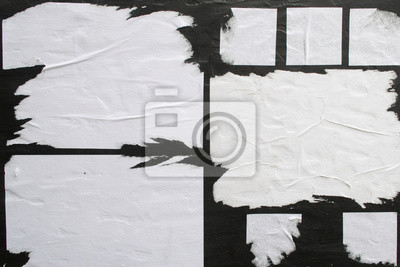 Plakat Several sheets of white paper pasted on a black wall.