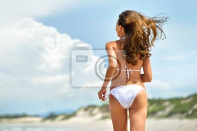 Sexy brunette jest uruchomiony na plaży, w stylowym bikini białym