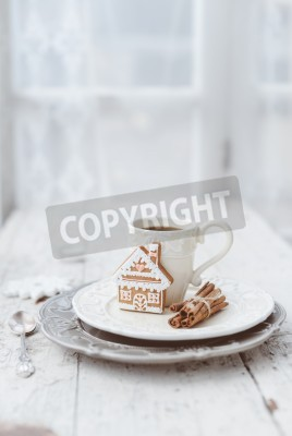 Plakat Shabby chic style coffee cup and plate with gingerbread house cookie, cinnamon sticks and other decorations for Christmas mood