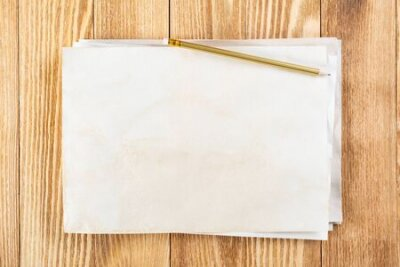Plakat Sheet of paper lying on wooden table. Blank white a4 format paper with pencil. Textured natural wooden background. Vintage copy space for design. Business planning and idea generation.