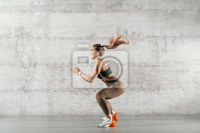 Plakat Side view of muscular focused brunette with ponytail and in sportswear jumping in front of brick wall in gym.