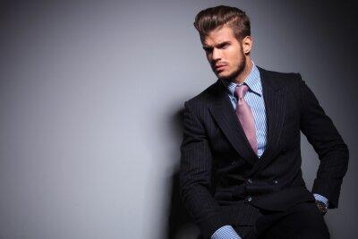 Plakat siedzi młoda modelka w garniturze patrzy w dal