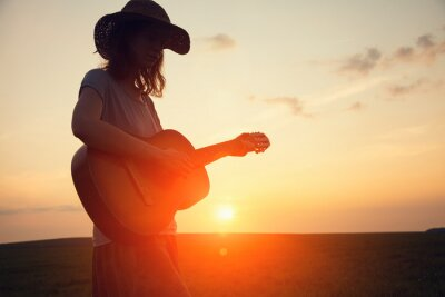 Plakat silhouette of young free woman in straw hat playing country music on a guitar at sunset, copy space