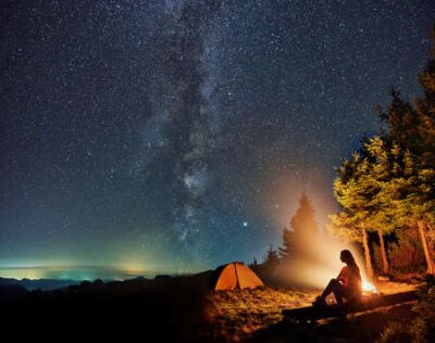 Plakat Silhouette of young woman sitting and resting near tent and campfire in the mountains. Concept of relaxation under starry sky with Milky way.