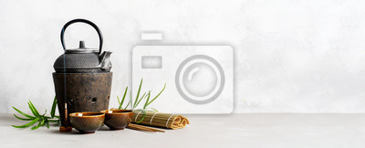 Plakat Simple still life with tea set, scattered tea, bamboo Mat, sticks, incense. Asian background with space for text.