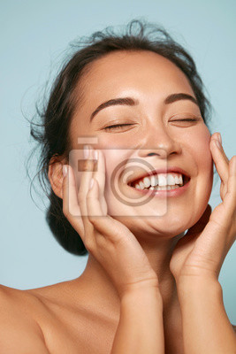 Plakat Skin care. Woman with beauty face touching healthy facial skin portrait. Beautiful smiling asian girl model with natural makeup touching glowing hydrated skin on blue background closeup