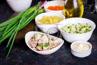 Składniki do przygotowania sałatki z wątroby dorsza z jajkami, ogórkami, ziemniakami i marchewką w miskach.
